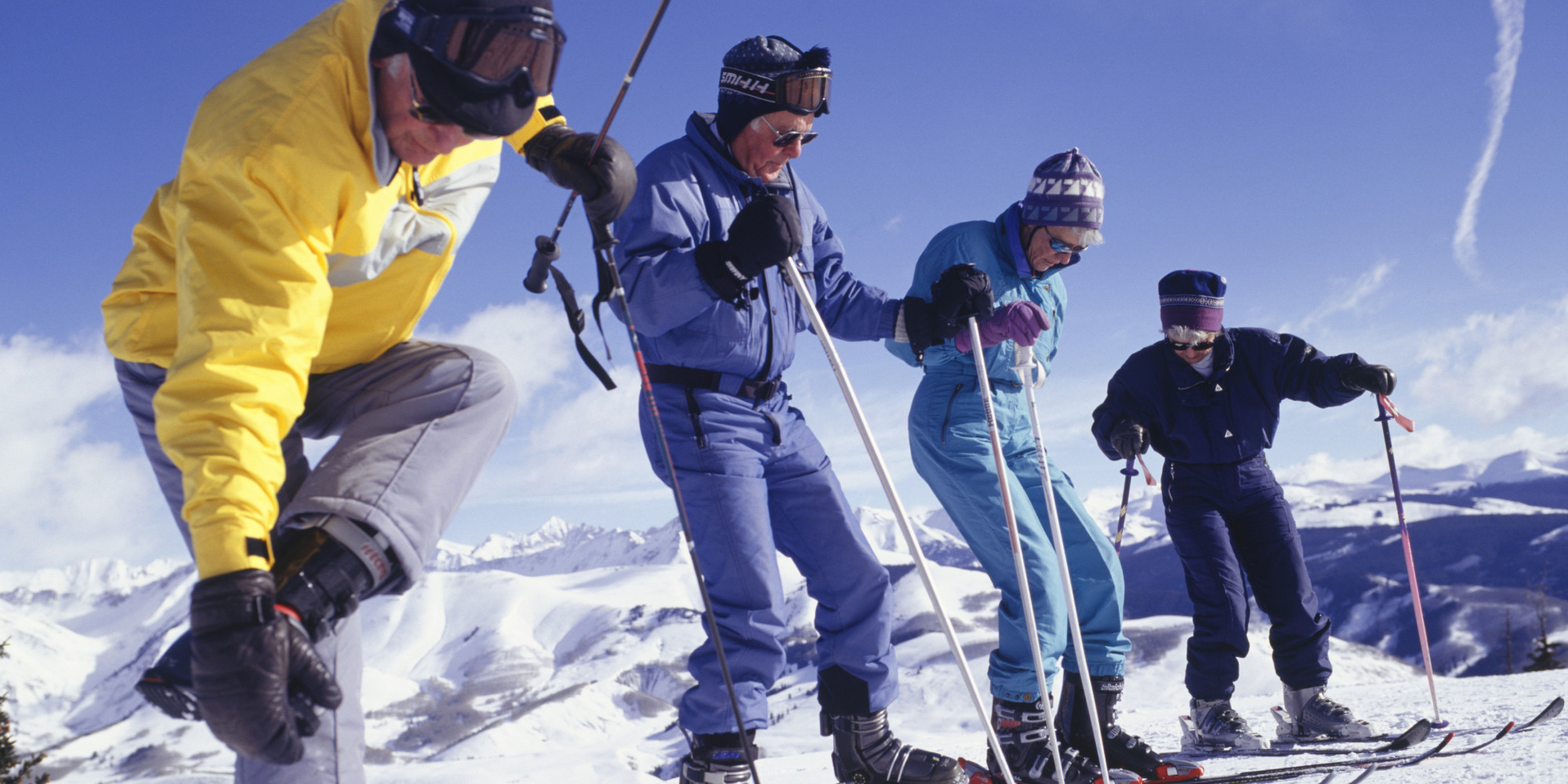 Four elderly people preparing to ski